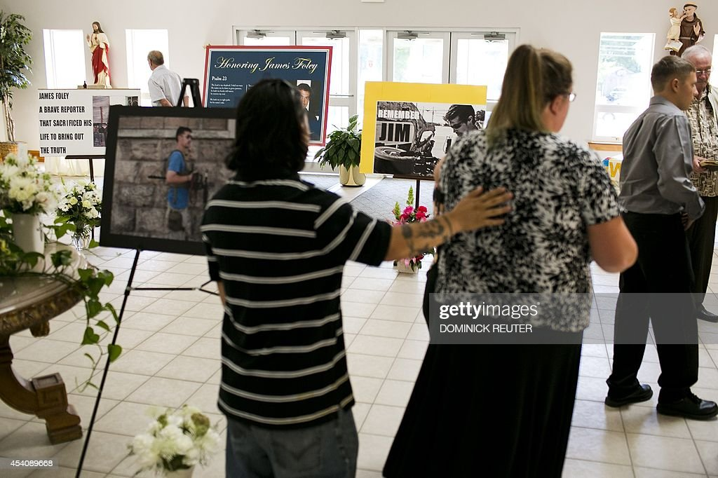 Parishioners walk past a display of photos of James Foley before a Catholic mass at Our Lady of the Holy Rosary Parish August 24, 2014 in Rochester, New Hampshire. The family and friends of murdered US journalist James Foley are attending the memorial mass and offering prayers for the safety of his fellow hostages in Syria.