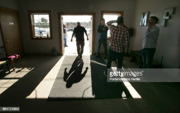 A parishoner walks out the door of the Machias Christian Fellowship church in Machias as Pastor Aaron Dudley back to camera at right talks to men in...
