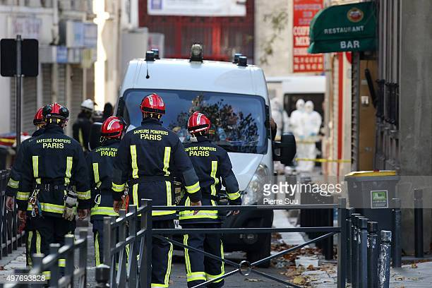 Parisian firefighters work on Rue des Corbillon in the northern Paris suburb of SaintDenis following a raid on an apartment on November 18 2015 in...