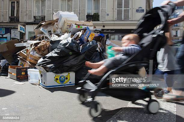 A Parisian pushes a stroller in front of rubbish bins in the Pigalle district in Paris on June 9 2016 One day before the start of Euro 2016 in France...