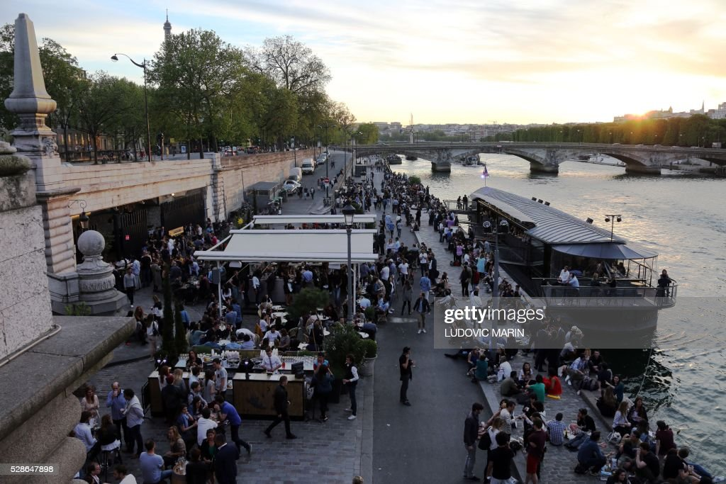 Parisians and tourists enjoy drinks and food after work along the river Seine at sunset, in Paris, on may 6, 2016. / AFP / LUDOVIC