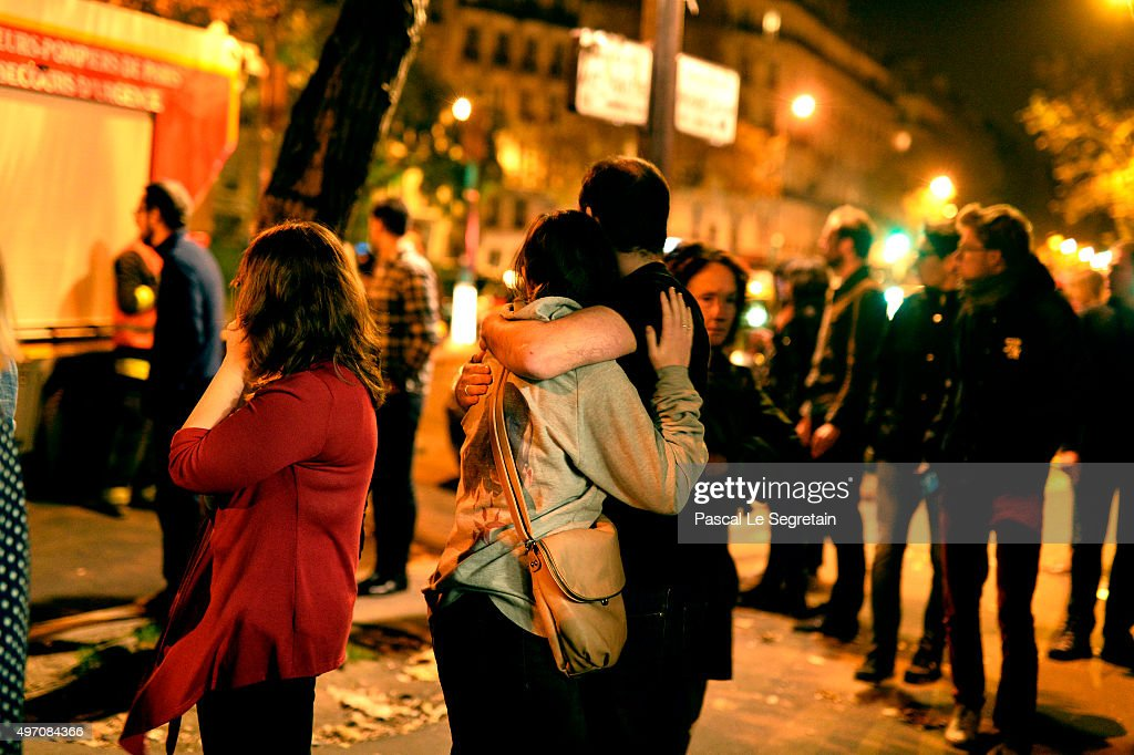 Parisians look at the scene outside the Bataclan concert hall after an attack on November 13 2015 in Paris France According to reports over 120...