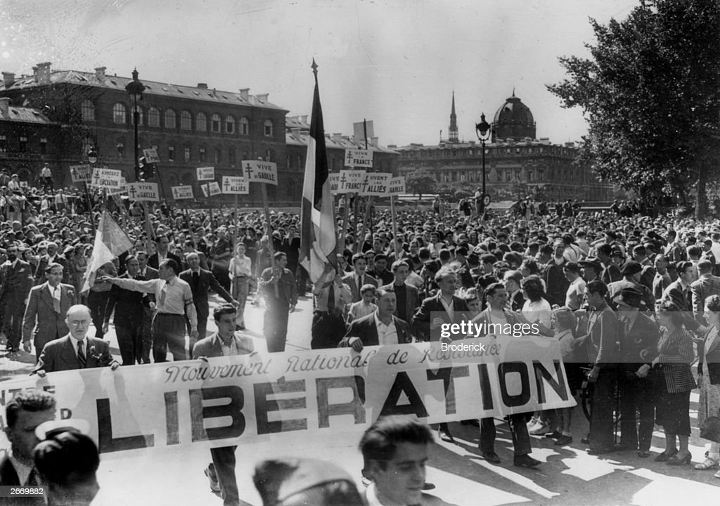 Parisians parading through the streets with banners, in celebration after the liberation of the French capital by the Allies.