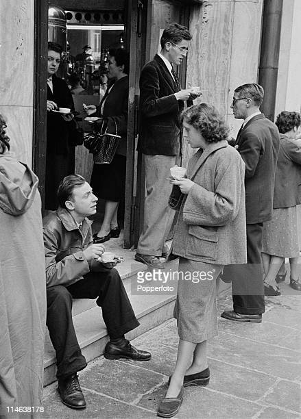 Parisians take their morning coffee on the pavement outside the Maison Du Cafe near the Place de l'Opera in Paris October 1953