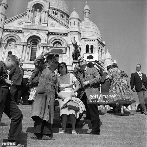 Parisiens essayant de regarder une éclipse solaire à l'aide de verres fumés sur les marches du SacréCoeur à Paris France le 2 octobre 1959
