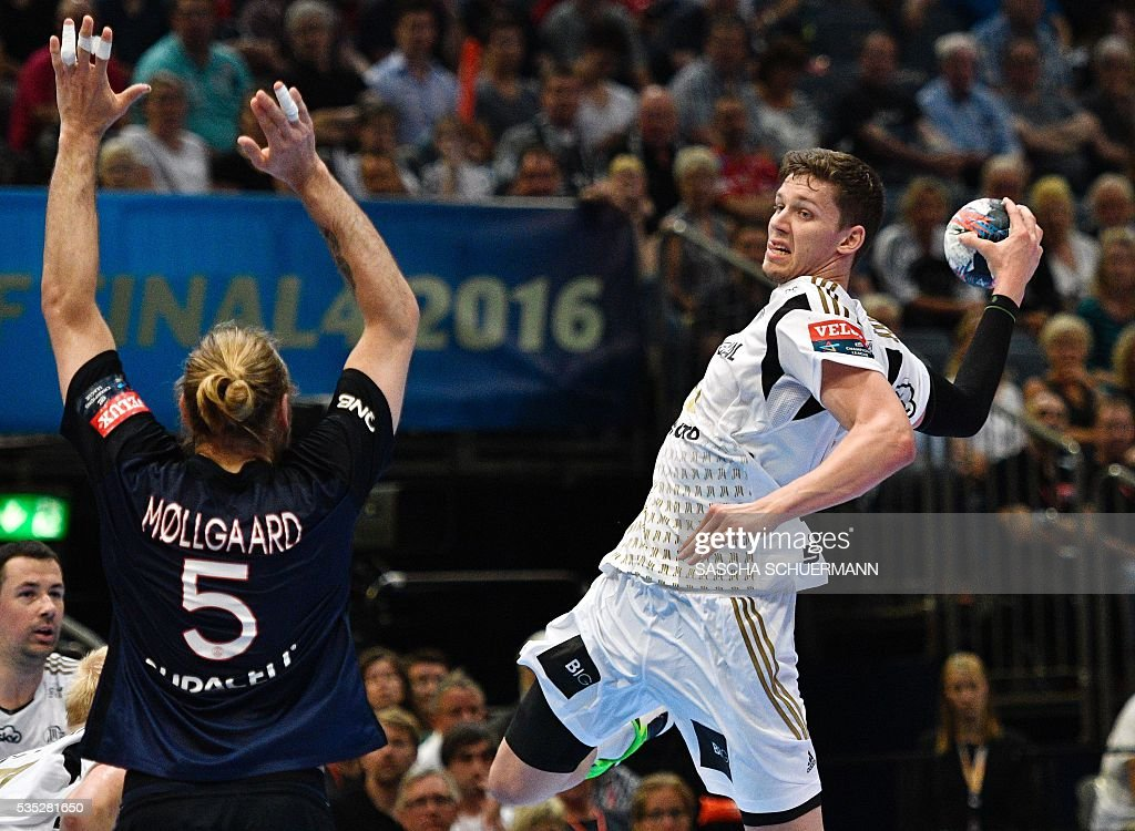 Paris's Henrik Mollgaard Jensen (L) and Kiel's Christian Dissinger vie for the ball during the Handball EHF Champions League final Four semifinal match between Paris St-Germain and THW Kiel in Cologne, western Germany, on May 29, 2016. / AFP / SASCHA