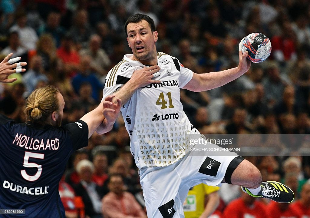 Paris's Henrik Mollgaard Jensen (L) and Kiel's Marko Vujin vie for the ball during the Handball EHF Champions League final Four semifinal match between Paris St-Germain and THW Kiel in Cologne, western Germany, on May 29, 2016. / AFP / SASCHA
