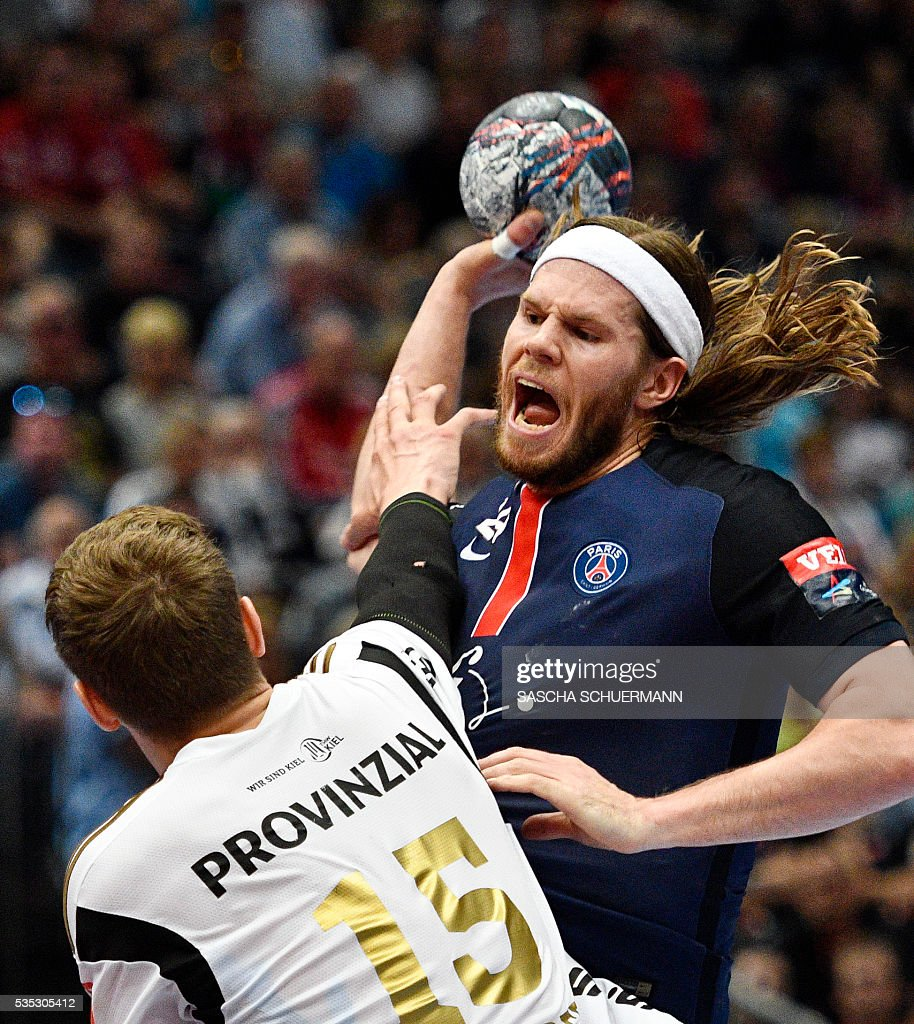 Paris's Mikkel Hansen (R) and Kiel's Christian Dissinger vie for the ball during the Handball EHF Champions League final Four semifinal match between Paris St-Germain and THW Kiel in Cologne, western Germany, on May 29, 2016. / AFP / SASCHA