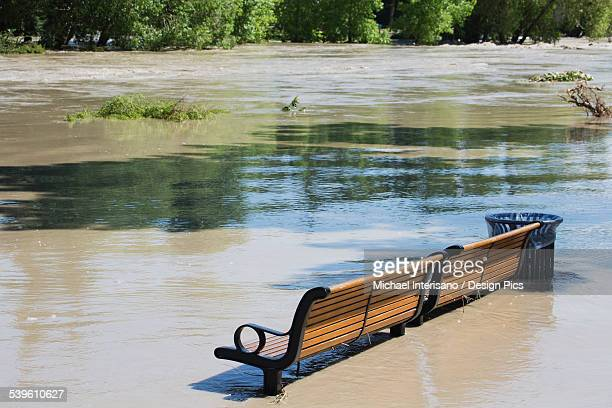 A Park Bench Sits In High Water After Flooding