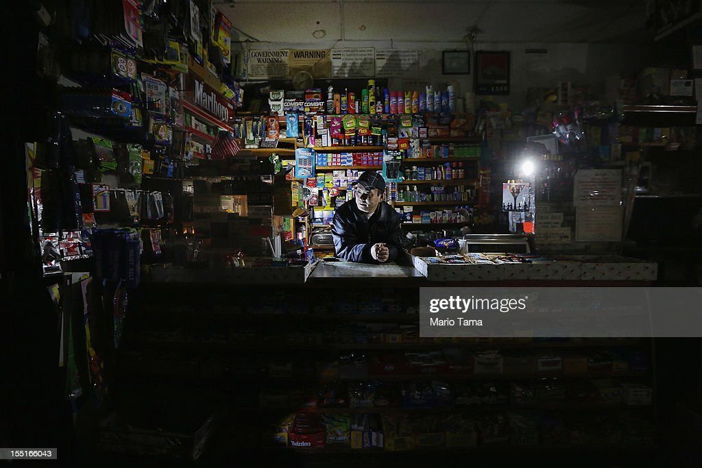 Park Choul waits behind the counter in his deli lit by flashlights in Manhattan's East Village following Superstorm Sandy on November 1, 2012 in New York City. Choul's deli remained open through the entire storm. East Village residents are still without power and some of the public housing buildings in the area flooded during the storm.