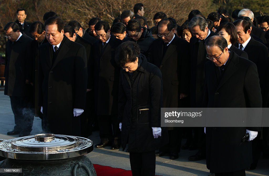 Park Geun Hye, South Korea's president-elect, center, observes a minute of silence on her visit to the National Cemetery in Seoul, South Korea, on Thursday, Dec. 20, 2012. Park, 60, of the ruling New Frontier Party, defeated main opposition nominee Moon Jae In, 51.6 percent to 48 percent, the biggest margin of victory in 25 years. Photographer: SeongJoon Cho/Bloomberg via Getty Images