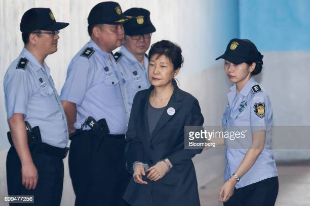 Park Geunhye former president of South Korea center is escorted by a prison officer as she arrives at the Seoul Central District Court in Seoul South...