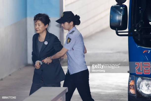 Park Geunhye former president of South Korea left is escorted by a prison officer as she arrives at the Seoul Central District Court in Seoul South...