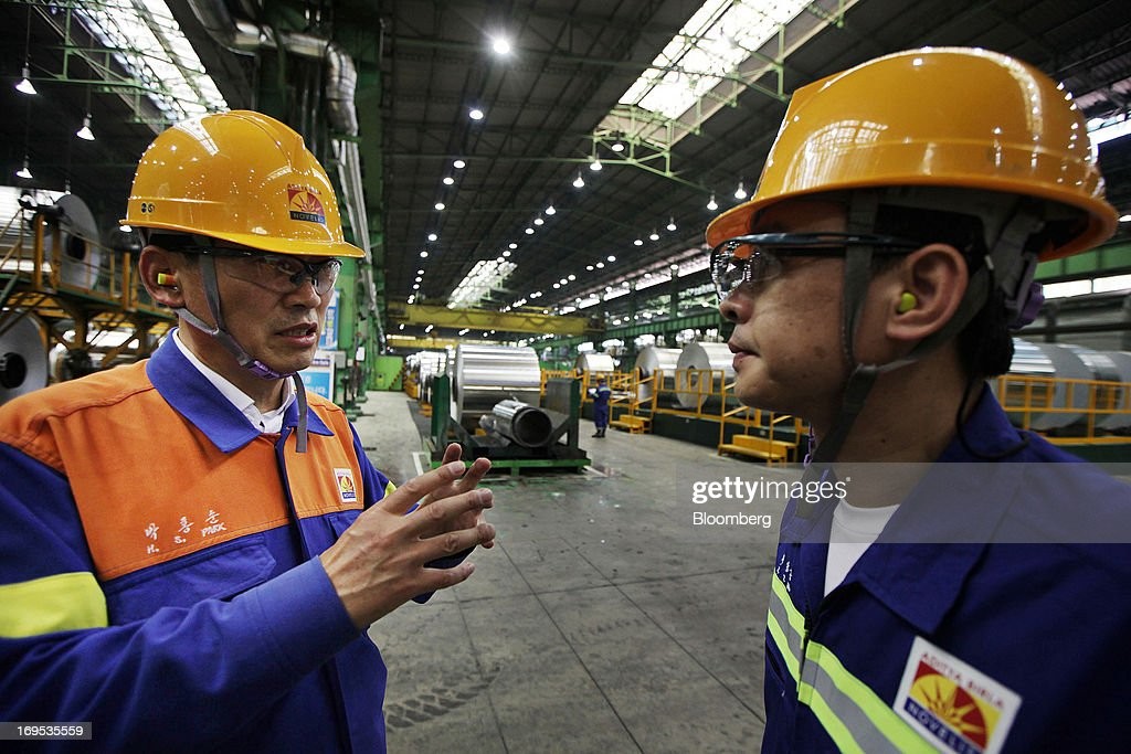 Park Hongsoon, plant manager of the Novelis Inc. Yeongju plant, left, talks to an employee at the company's production facility in Yeongju South Korea, on Thursday, May 23, 2013. Novelis plans to boost research and development staff by 40 percent as the biggest supplier of flat-rolled aluminum products to global carmakers seeks to increase recycled content in products used in cans and vehicles. Photographer: Woohae Cho/Bloomberg via Getty Images