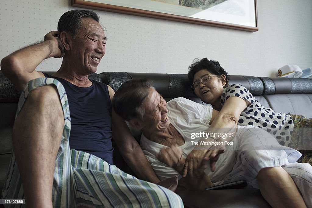 Park Hyang-sook(right), 75, embraces and tickles Han Byung-soo, 82, and Lee Bong-Jeon smiles at them at a care house on July 10, 2013 in Seoul, South Korea. Park escaped from North Korea with her late husband's remains in 2006. Park's late husband was POW. Han escaped from a coal mine in North Korea in 2004 and Lee escaped did the same in North Korea in 2005.