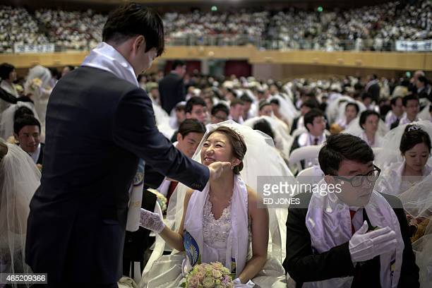 Park HyunSung gestures to his bride Park JeongMin at their seats at the venue of their mass wedding ceremony at the headquarters of the Unification...