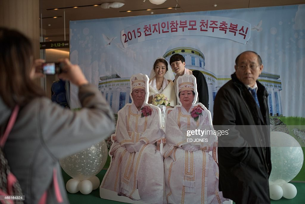 Park Hyun-Sung (centre R), 31, poses for a photo with a cutout of church founder the late <a gi-track='captionPersonalityLinkClicked' href=/galleries/search?phrase=Sun+Myung+Moon&family=editorial&specificpeople=773635 ng-click='$event.stopPropagation()'>Sun Myung Moon</a> and his wife Hak Ja Han, with his new wife Park Jeong-Min (centre L), 28, following their mass wedding ceremony at the headquarters of the Unification Church in Gapyeong on March 3, 2015. Some 3,800 couples participated in the ceremony in Gapyeong, east of the capital Seoul. The church's mass weddings began in the early 1960s and at first involved just a few dozen couples, though numbers mushroomed over the years. The teachings of the Unification Church are based on the Bible but with new interpretations. The late founder <a gi-track='captionPersonalityLinkClicked' href=/galleries/search?phrase=Sun+Myung+Moon&family=editorial&specificpeople=773635 ng-click='$event.stopPropagation()'>Sun Myung Moon</a> saw his role as completing the unfulfilled mission of Jesus to restore humanity to a state of 'sinless' purity. AFP PHOTO / Ed Jones
