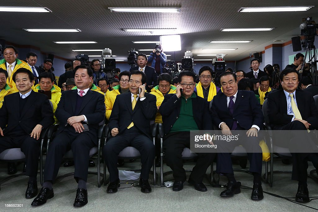 Park Jie Won, floor leader of the main opposition Democratic United Party, third from right, talks on a mobile phone as he and other party members monitor exit poll results for the presidential election at the party's headquarters in Seoul, South Korea, on Wednesday, Dec. 19, 2012. South Korean ruling party presidential candidate Park Geun Hye leads opposition nominee Moon Jae In in a close race to lead Asia's fourth-biggest economy, exit polls showed. Photographer: SeongJoon Cho/Bloomberg via Getty Images