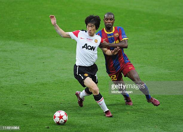 Park JiSung of Manchester United is challenged by Eric Abidal of FC Barcelona during the UEFA Champions League final between FC Barcelona and...