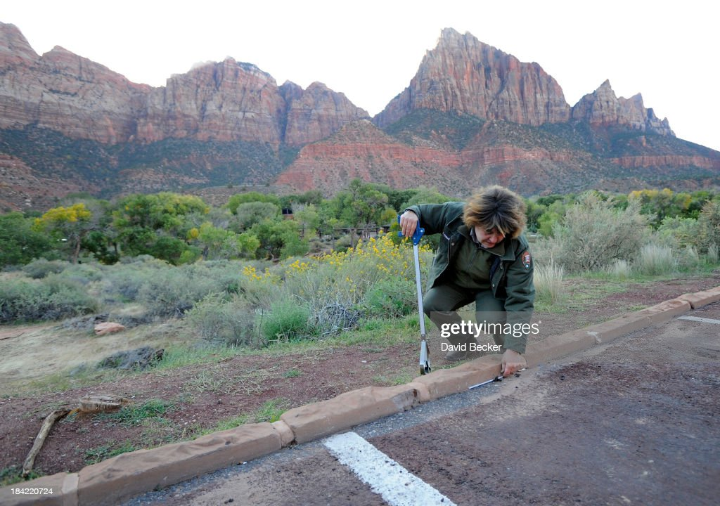 Park maintaince worker Therese Feinquer picks up trash in a parking area in Zion National Park on October 12, 2013 in Springdale, Utah. The Obama administration said it would allow states to use their own money to reopen some national parks after a handful of governors made the request. Utah Gov. Gary Herbert said he reached an agreement to pay $166,572 a day to the Interior Department to open eight national sites in Utah.