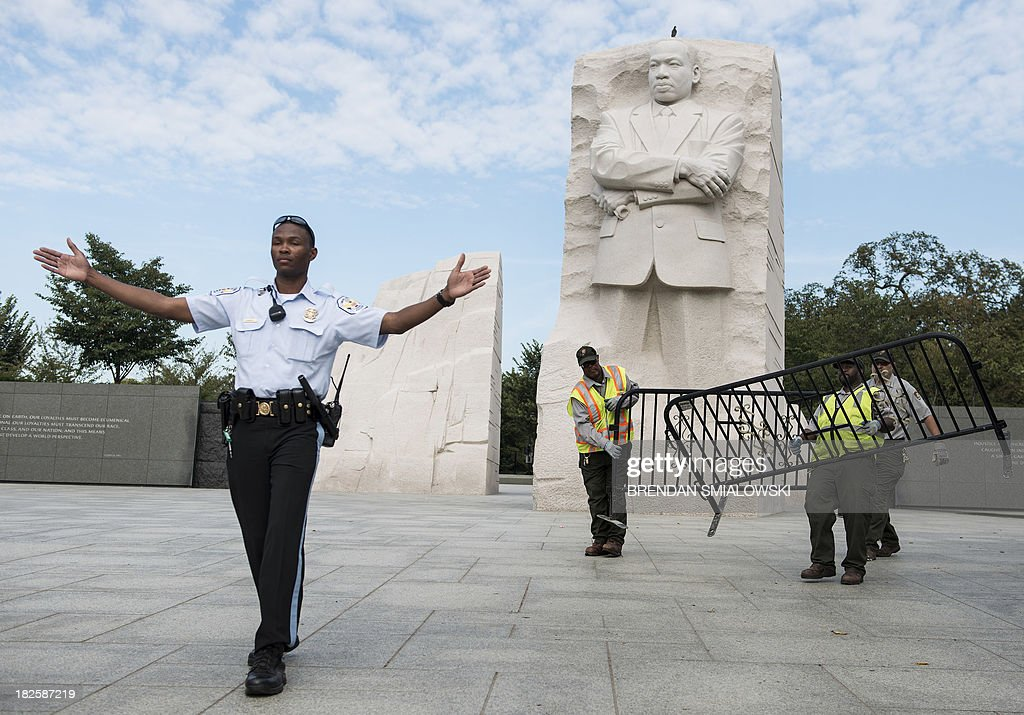 Park Police Officer and National Park Service employees close the Martin Luther King Jr. Memorial on the National Mall October 1, 2013 in Washington, DC. The US government is in a forced shutdown after lawmakers failed to pass a spending bill last night. AFP PHOTO/Brendan SMIALOWSKI