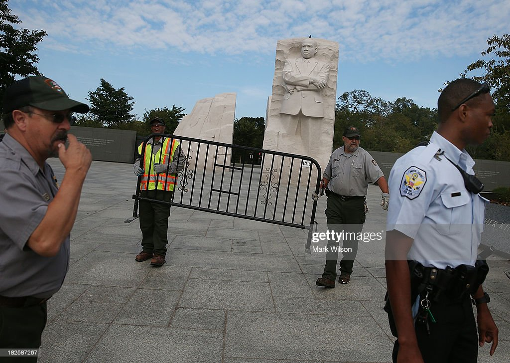 S. Park Police officer assists Park Service employees in closing down the Martin Luther King (MLK) Memorial on the National Mall October 1, 2013 in Washington, DC. The National Mall and all monuments and large sections of the government are closed due to the government shutdown after Congress failed to agree on a federal budget for the first time in 17 years.