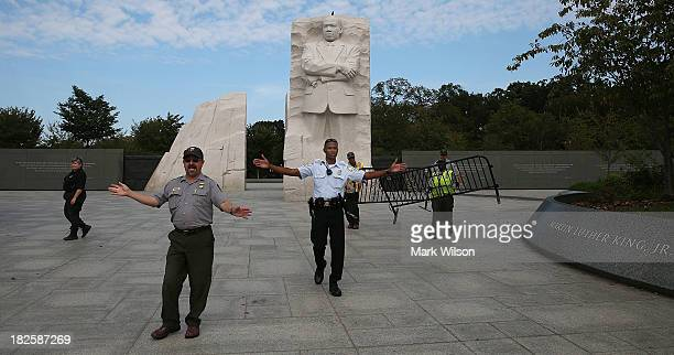 S Park Police officer assists Park Service employees in closing down the Martin Luther King Memorial on the National Mall October 1 2013 in...