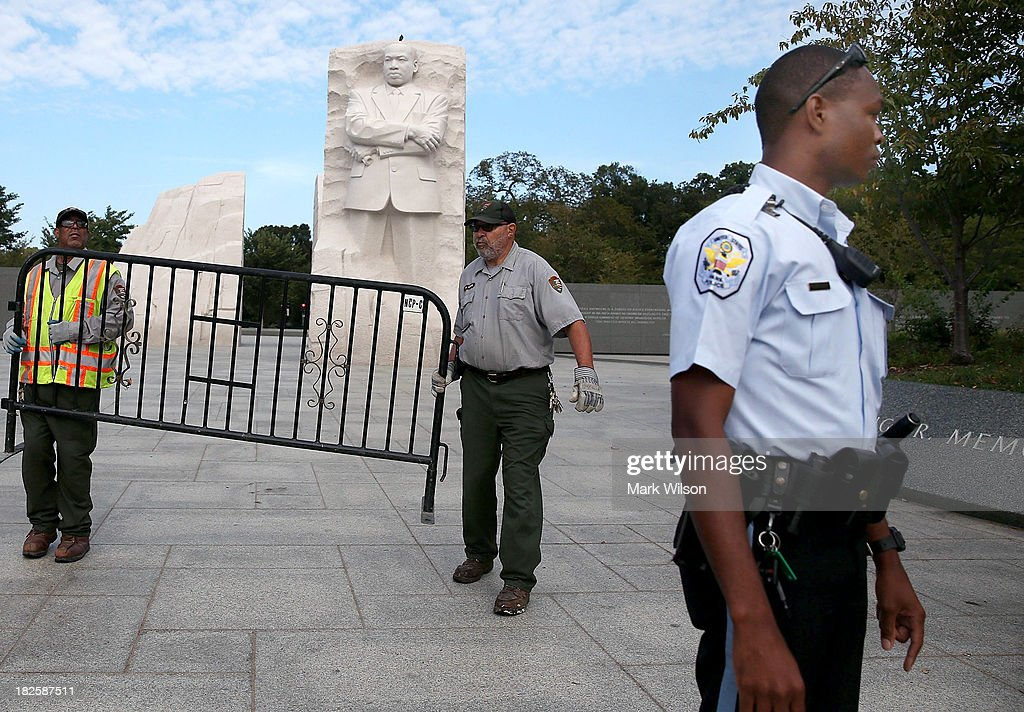 S. Park Police officer (R) assists U.S. Park Service employees in closing down the Martin Luther King (MLK) Memorial on the National Mall October 1, 2013 in Washington, DC. The National Mall and all monuments and large sections of the government are closed due to the government shutdown after Congress failed to agree on a federal budget for the first time in 17 years.
