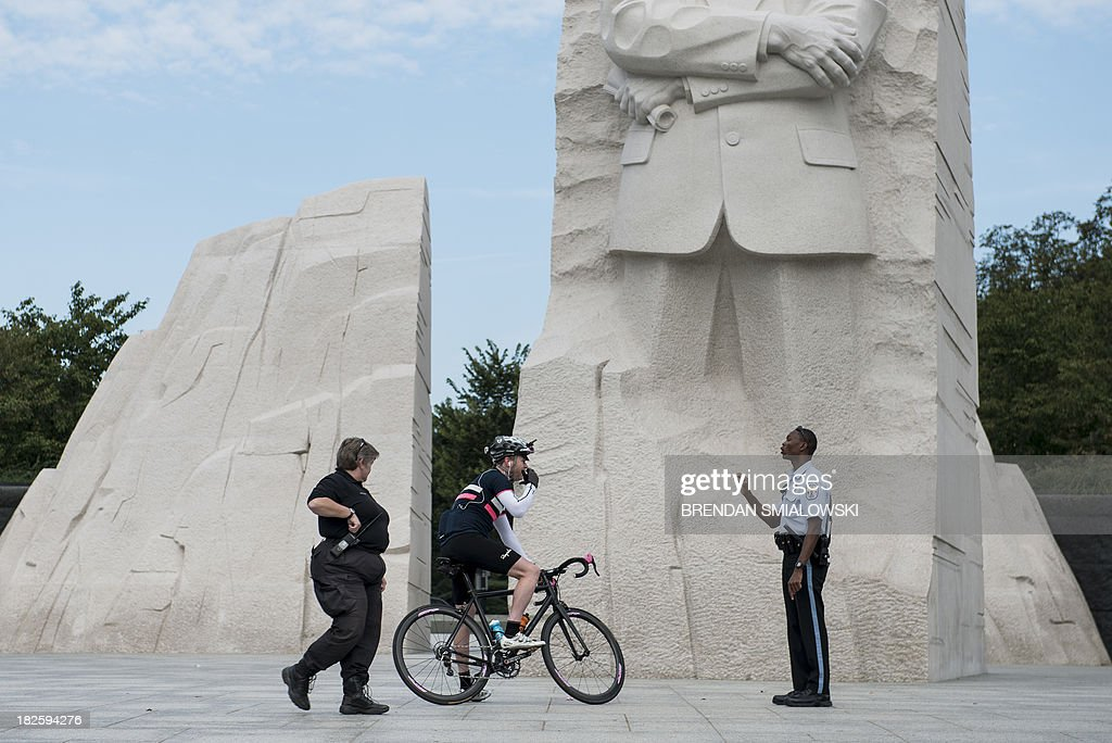 US Park Police Officers speak to a biker while closing the Martin Luther King Jr. Memorial on the National Mall October 1, 2013 in Washington, DC. The US government is in a forced shutdown after lawmakers failed to pass a spending bill last night. AFP PHOTO/Brendan SMIALOWSKI
