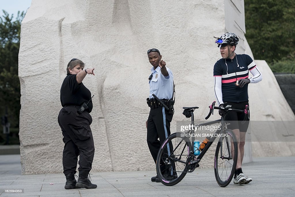 US Park Police Officers yell at a biker while closing the Martin Luther King Jr. Memorial on the National Mall October 1, 2013 in Washington, DC. The US government is in a forced shutdown after lawmakers failed to pass a spending bill last night. AFP PHOTO/Brendan SMIALOWSKI