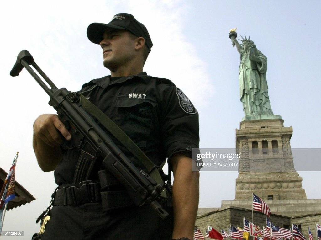 US Park Police SWAT Team officer Michael Fermaint stands guard in front of the Statue of Liberty on Liberty Island 03 August 2004.The Statue's pedestal was opened to the public for the first time since the 11 September, 2001 terrorist attacks. The higher reaches of the statue -- the crown requires a climb of 354 steps, or some 22 storeys -- cannot cope with large numbers of tourists and the access route also fails certain safety standards. As a result, it remains closed to the public. AFP PHOTO Timothy A. CLARY