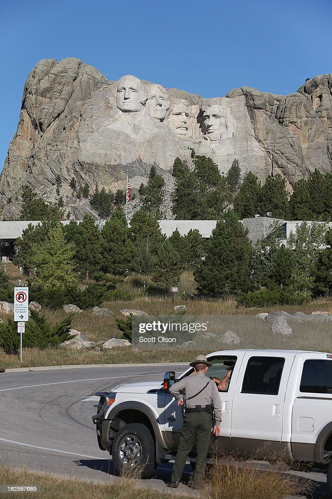 A park ranger chats with a motorist outside the entrance to Mount Rushmore National Memorial on October 1, 2013 in Keystone, South Dakota. Mount Rushmore and all other national parks were closed today after congress failed to pass a temporary funding bill, forcing about 800,000 federal workers off the job. A bulletin issued by the Department of Interior states, 'Effective immediately upon a lapse in appropriations, the National Park Service will take all necessary steps to close and secure national park facilities and grounds in order to suspend all activities ...Day use visitors will be instructed to leave the park immediately...'