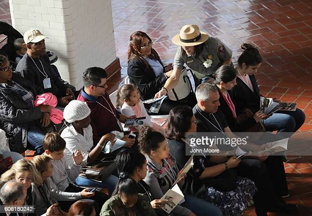 S park ranger hands out flyers to immigrant families before a naturalization ceremony on Ellis Island on September 16 2016 in New York City The...