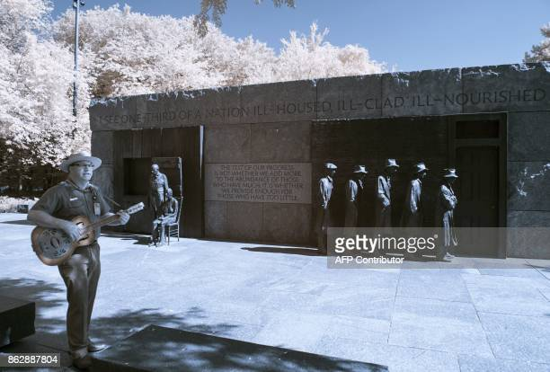 A Park Ranger plays guitar near a sculpture at the Franklin Delano Roosevelt Memorial in Washington DC on September 20 2017 / AFP PHOTO / Andrew...