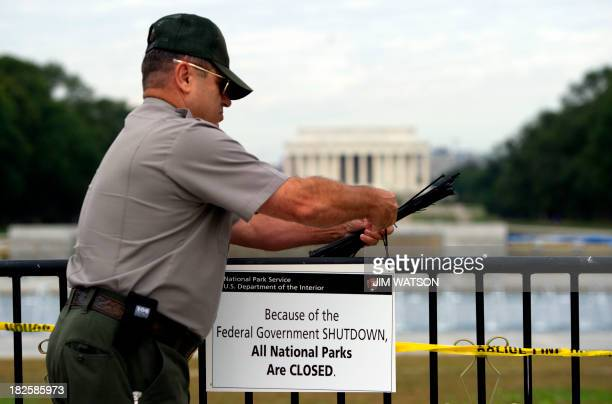 US Park Ranger Richard Trott places a closed sign on a barricade in fron tof the World War II monument in Washington DC October 1 due to a US...