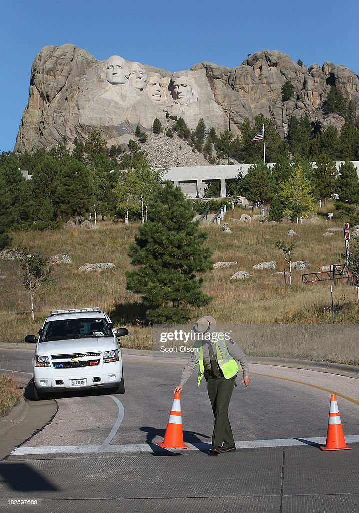 A park ranger secures a road at the entrance to Mount Rushmore National Memorial on October 1, 2013 in Keystone, South Dakota. Mount Rushmore and all other national parks were closed today after congress failed to pass a temporary funding bill, forcing about 800,000 federal workers off the job. A bulletin issued by the Department of Interior states, 'Effective immediately upon a lapse in appropriations, the National Park Service will take all necessary steps to close and secure national park facilities and grounds in order to suspend all activities ...Day use visitors will be instructed to leave the park immediately...'