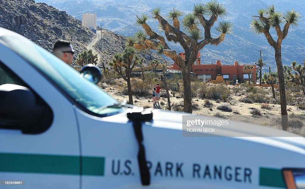 Park Ranger (L) stands guard at the gate of closed Joshua Tree National Park as two French tourists explore the landscape outside the park's perimeter, in Joshua Tree, California on October 2, 2013, the second day of the US government shutdown. Hundreds of tourists staying in landmark US national parks like Yosemite and the Grand Canyon face a deadline October 3, 2013 to leave due to the government shutdown. The National Park Service closed its gates on its 401 sites as soon as the shutdown went into effect Tuesday morning, October 1, 2013, leaving visitors -- including many from overseas -- frustrated at park entrances across the country. AFP PHOTO / Robyn Beck