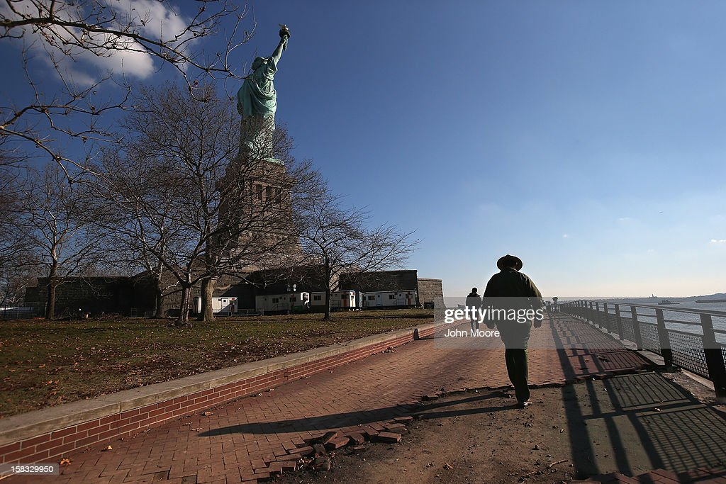 A park ranger walks along a damaged boardwalk around the Statue of Liberty which, remains closed to tourists six weeks after Hurricane Sandy on December 13, 2012 in New York City. The storm caused extensive damage to National Park Service facilities on Liberty Island, although the statue itself remained unscathed, according to Secretary of the Interior Ken Salazar, who toured the island Thursday.