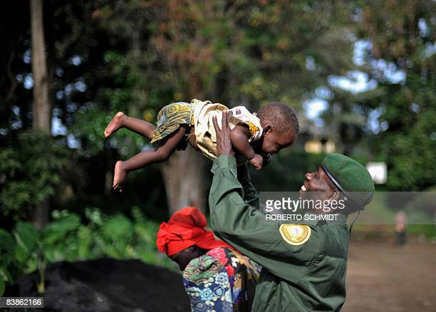 A park ranger working in the Virunga National Park smiles at his 9monthold daughter after they and other park ranger families came back to their...