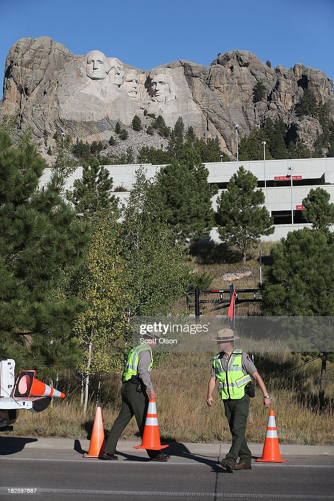 Park rangers block off the shoulder of the highway to prevent motorists from pulling off the highway outside Mount Rushmore National Memorial on October 1, 2013 in Keystone, South Dakota. Mount Rushmore and all other national parks were closed today after congress failed to pass a temporary funding bill, forcing about 800,000 federal workers off the job. A bulletin issued by the Department of Interior states, 'Effective immediately upon a lapse in appropriations, the National Park Service will take all necessary steps to close and secure national park facilities and grounds in order to suspend all activities ...Day use visitors will be instructed to leave the park immediately...'