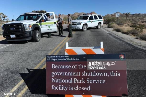 US Park Rangers stand at the closed gate to Joshua Tree National Park in Joshua Tree California on October 2 the second day of the US government...