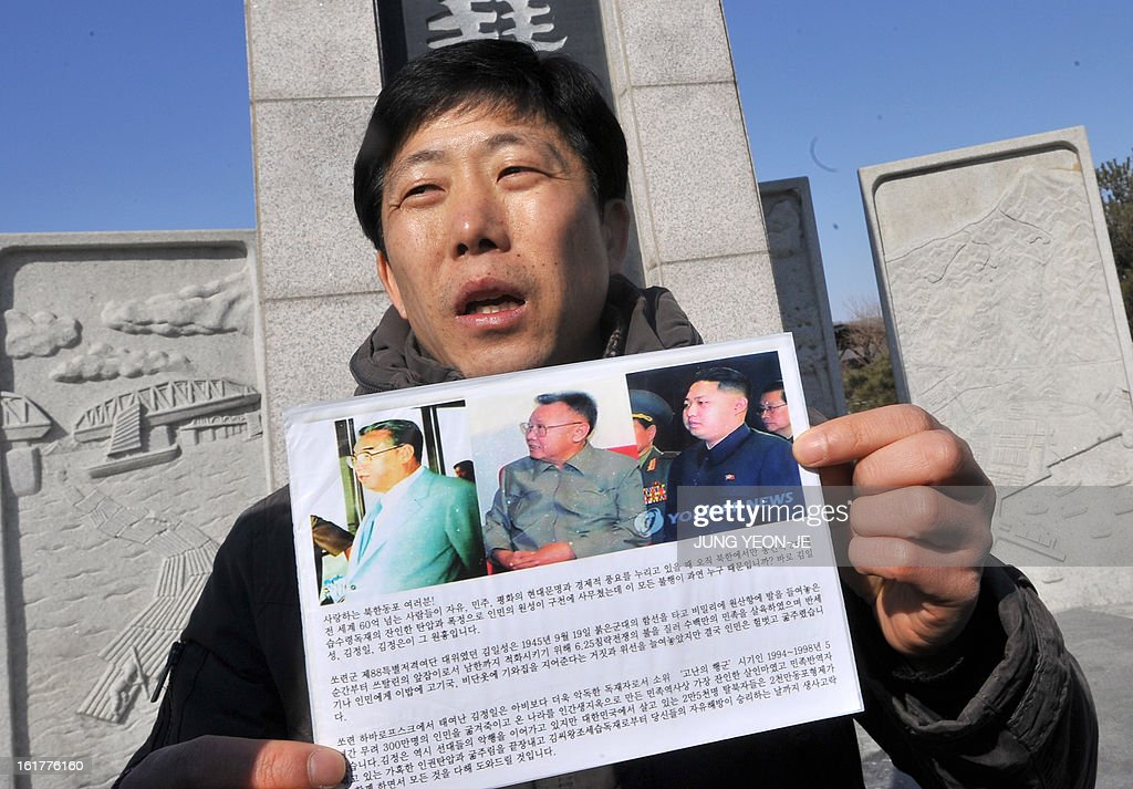 Park Sang-Hak, a former North Korean defector, holds an anti-Pyongyang leaflet showing portraits of North Korea's ruling Kim family at Imjingak park near the inter-Korean border in Paju on February 16, 2013. Activists launched balloons across the border carrying leaflets that criticise North Korea's ruling Kim family on the birth anniversary of late leader Kim Jong-Il, amid high tension over its long-range rocket launch and nuclear test. AFP PHOTO / JUNG YEON-JE