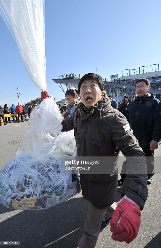 Park Sang-Hak, a former North Korean defector, prepares to float a balloon carrying anti-Pyongyang leaflets at Imjingak park near the inter-Korean border in Paju on February 16, 2013. Activists launched balloons across the border carrying leaflets that criticise North Korea's ruling Kim family on the birth anniversary of late leader Kim Jong-Il, amid high tension over its long-range rocket launch and nuclear test.