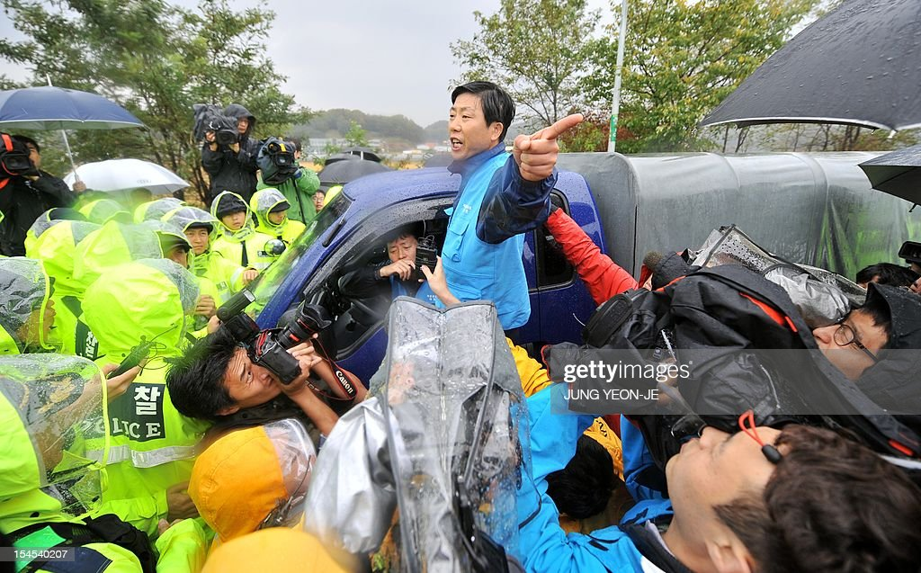 Park Sang-Hak (C), an activist and former defector from North Korea, complains as policemen block his truck containing anti-North Korea leaflets on a roadway in Paju, north of Seoul, on October 22, 2012. South Korean troops and riot police prevented activists from launching anti-Pyongyang leaflets across the border, after North Korea threatened a 'merciless' military response.