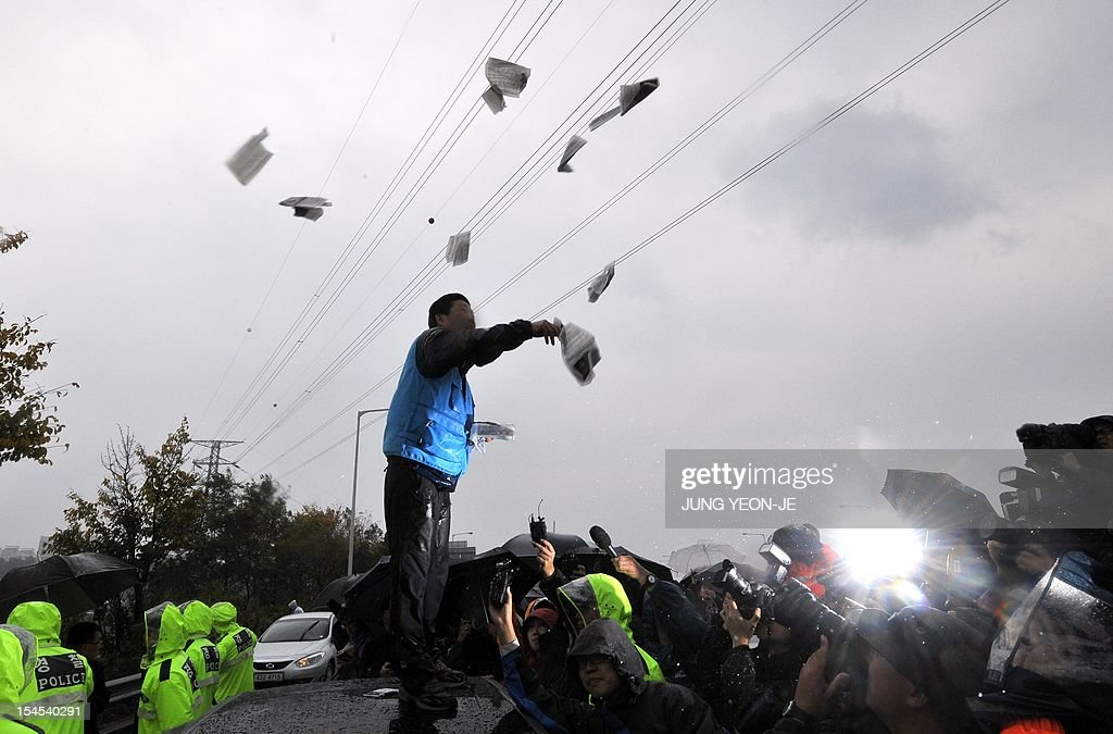 Park Sang-Hak (C), an activist and former defector from North Korea, scatters anti-Pyongyang leaflets as police block his planned rally near the tense border on a roadway in Paju, north of Seoul, on October 22, 2012. South Korean troops and riot police prevented activists from launching anti-Pyongyang leaflets across the border, after North Korea threatened a 'merciless' military response.