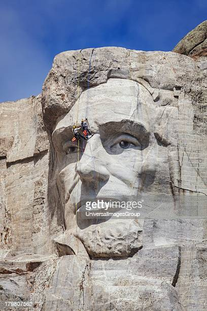 Park service employees rappel down Lincolns face while conducting an inspection of Mount Rushmore Mount Rushmore National Monument South Dakota