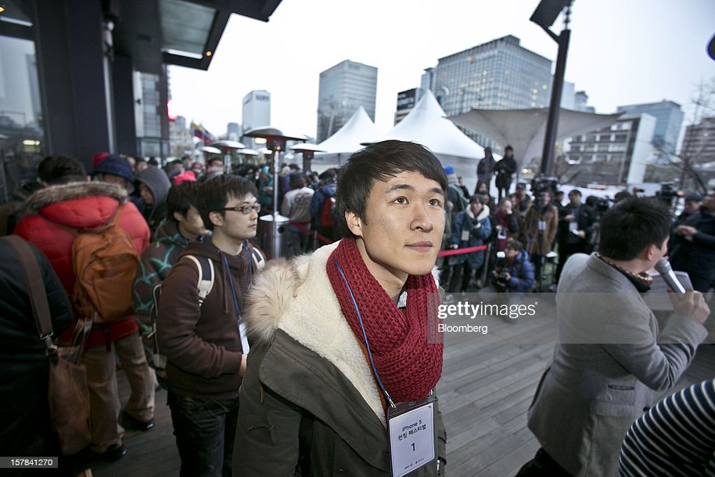Park Seul-gi, 27, first in the queue for Apple Inc.'s iPhone 5, stands outside a KT Corp. Olleh brand mobile phone store before the doors open in Seoul, South Korea, on Friday, Dec. 7, 2012. The iPhone 5 went on sale in South Korea today. Photographer: Jean Chung/Bloomberg via Getty Images