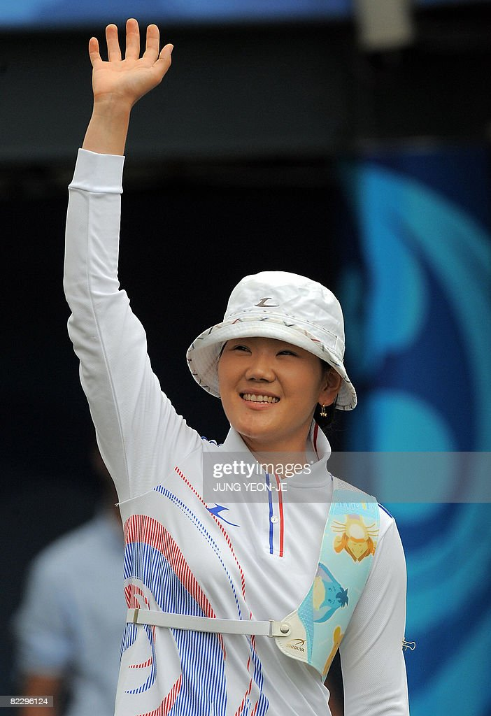 Park Sung-Hyun of South Korea waves to the crowd after she sets a new Olympic record with a score 155 in the women's individual archery 1/8 eliminations event during the 2008 Beijing Olympic Games at the Olympic Green archery field on August 14, 2008.