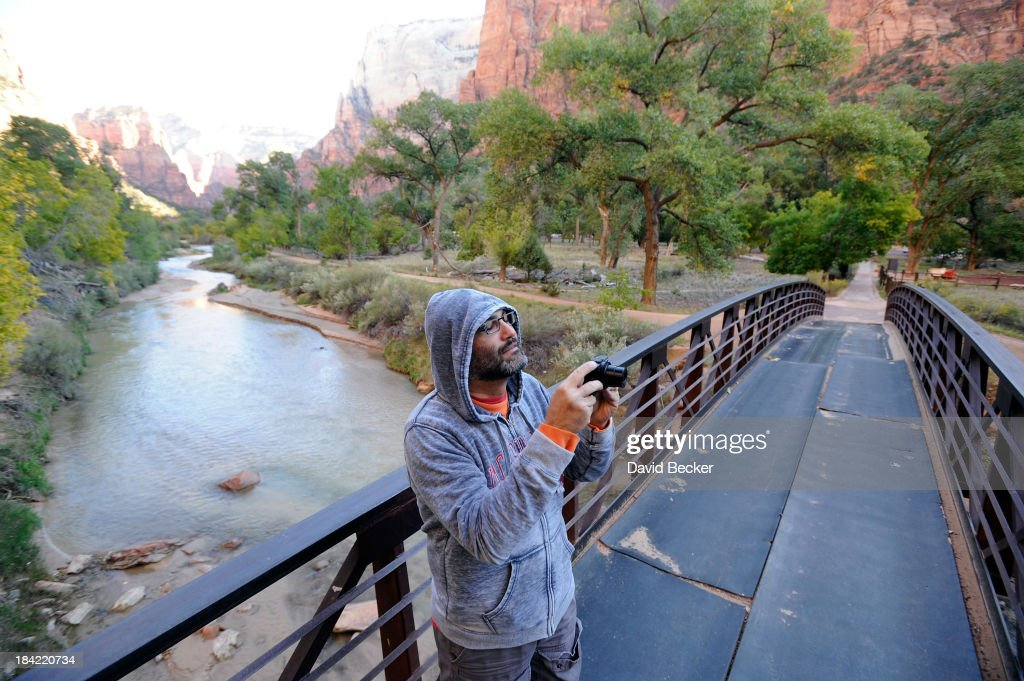 Park visitor Kayvan Khiabani of Las Vegas, Nevada, photographs the scenery above the north fork of the Virgin River in the now opened Zion National Park on October 12, 2013 in Springdale, Utah. The Obama administration said it would allow states to use their own money to reopen some national parks after a handful of governors made the request. Utah Gov. Gary Herbert said he reached an agreement to pay $166,572 a day to the Interior Department to open eight national sites in Utah.