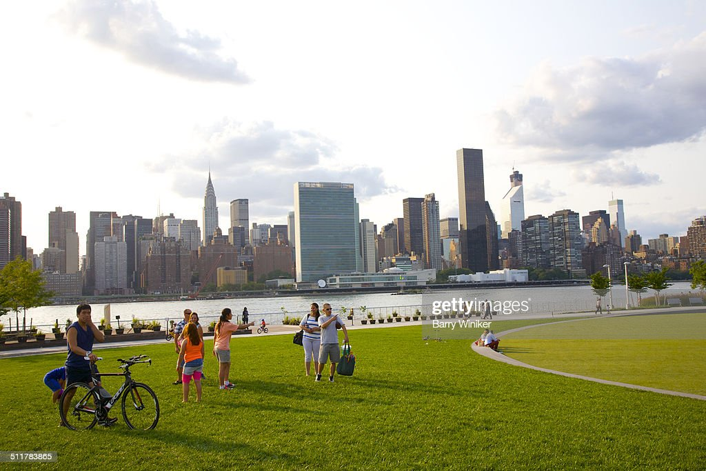 Park visitors standing on grass near NYC view